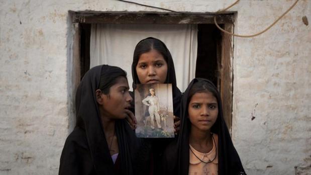 Las hijas de Asia Bibi posan con una foto de su madre