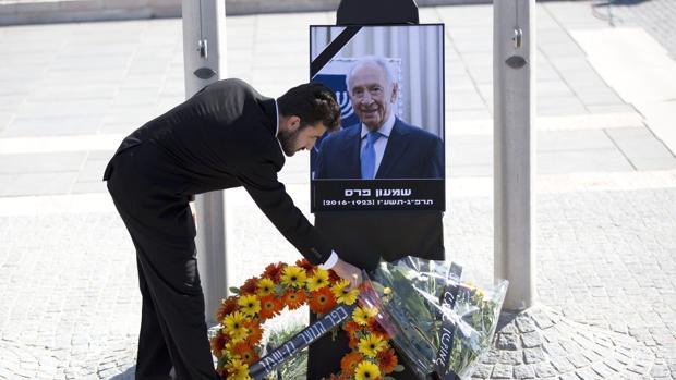 Un israelí coloca flores ante un retrato del expresidente israelí Simon Peres durante un acto público celebrado en el Parlamento o Kneset, en Jerusalén