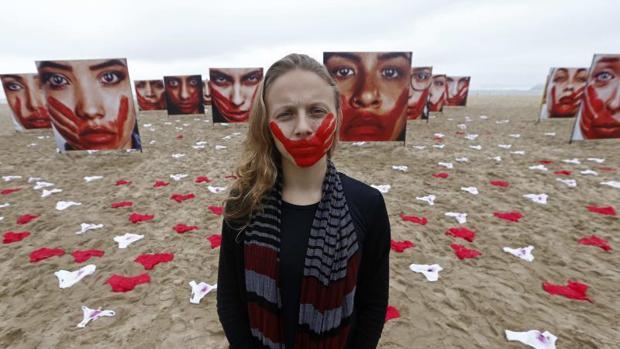 Una voluntaria de la ONG Río de Paz posa en la playa de Copacabana, junto a imágenes de modelos que representan a mujeres que sufrieron algún tipo de abuso sexual