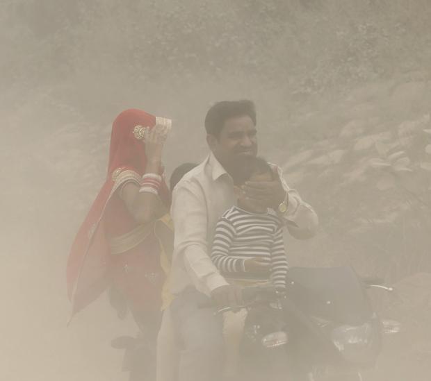 Una familia circula en moto en Nueva Delhi en medio de una espesa niebla causada por la contaminación