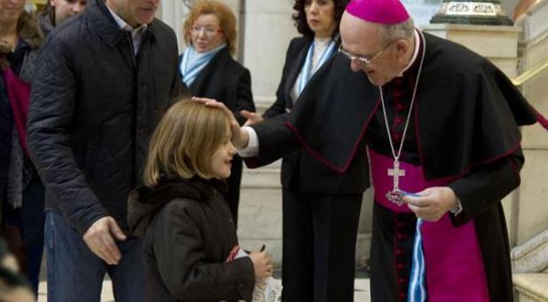 Monseñor Carlos Osoro bendice a una niña en la catedral de La Almudena durante la pasada misa de la familia