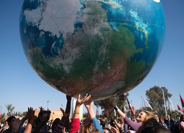 Asistentes a la Cumbre juegan con un globo terráqueo hinchable
