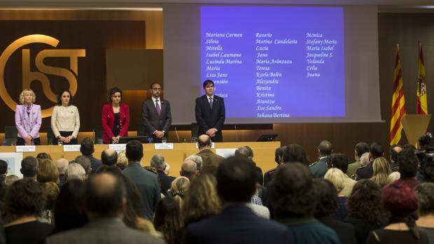 La ministra de Sanidad, en el centro de rojo, guarda un minuto de silencio en Barcelona por las víctimas de la violencia de género de 2019: 39 mujeres, con nombres y apellidos reflejados en la pantalla