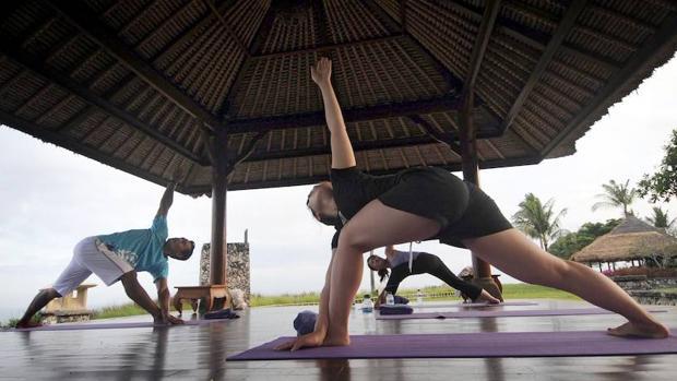 Un grupo de personas practica yoga