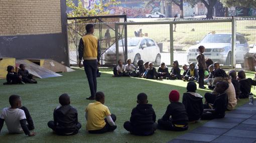 Los alumnos de la escuela Jeppe Park Primary en su recreo, tras la valla otros niños jugando al fútbol en el parque.