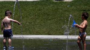 Unos niños se bañan en una fuente para combatir el calor