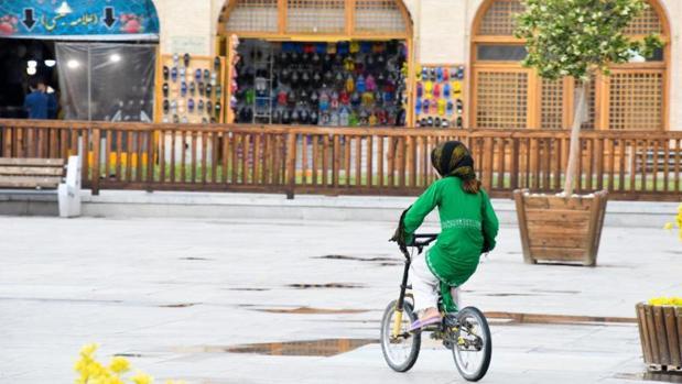 Una joven iraní pasea en su bicicleta