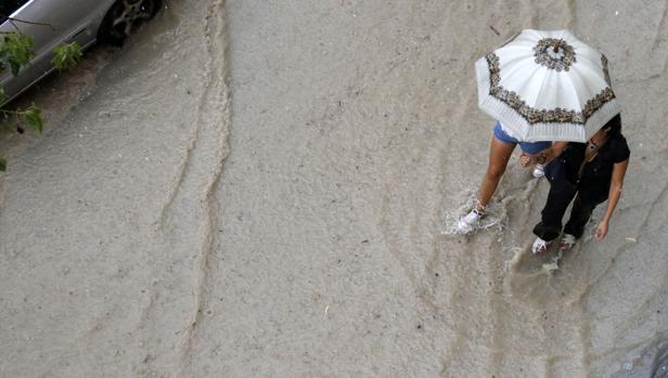 Dos mujeres caminan por la calle en plena inundación