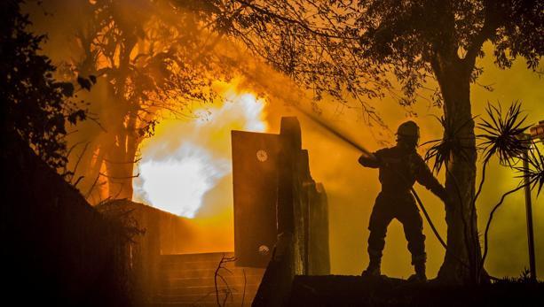 Un bombero trabaja en la extinción de un incendio en Funchal, isla de Madeira