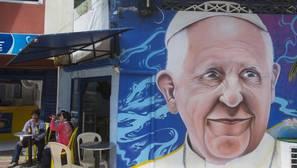 Residentes comparten en un local junto a un mural con la imagen del papa Francisco hoy, 6 de septiembre de 2017, en Villavicencio (Colombia)