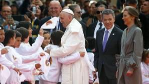 Un niño saluda al Papa con un abrazo en presencia de Juan Manuel Santos, presidente del país, y su esposa