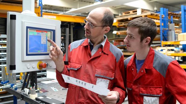 Un aprendiz alemán atiende a las explicaciones de su superior en una empresa metalúrigca