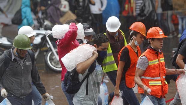 Jóvenes voluntarios llevan alimentos a un centro de abastecimiento para los damnificados