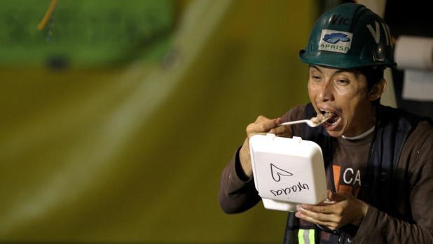 Un miembro de las brigadas de rescate recibe comida de varios ciudadanos en agradecimiento por su labor
