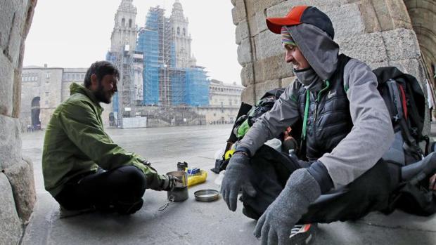 Dos peregrinos checos que llegaron desde Bordeaux (Francia), se cobijan del frío con un hornillo debajo de los arcos del palacio de Raxoi, este miércoles en la plaza de Obradoiro, Santiago de Compostela