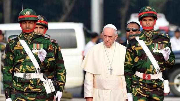 El Papa Francisco (c) pasa revista a la guardia de honor a su llegada al Aeropuerto Internacional de Daca (Bangladesh)