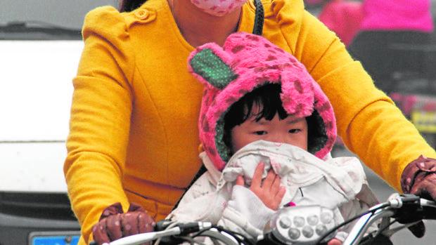 Una mujer y su hijo se protegen del «smog»