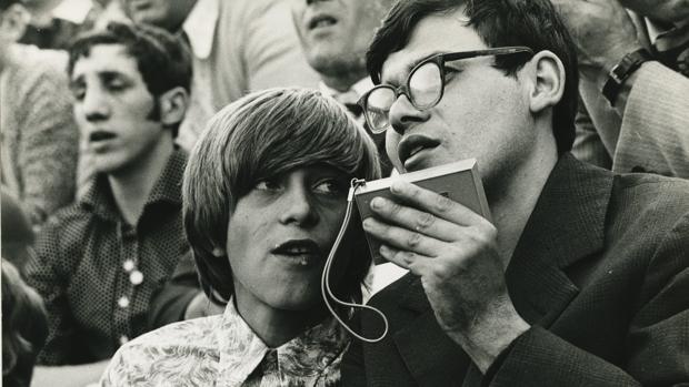 Dos personas usan un transistor para escuchar un partido de fútbol