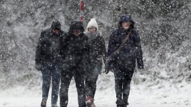 Un grupo de personas, andando bajo la nieve en España