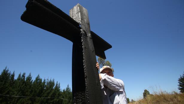 Un hombre se apoya en una cruz en Cunco, en la región chilena de Araucania