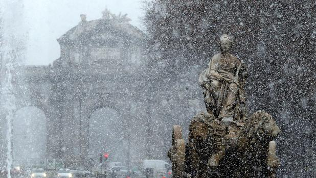 Vista de la fuente de Cibeles bajo la intensa nevada caída esta mañana en el centro de la capital
