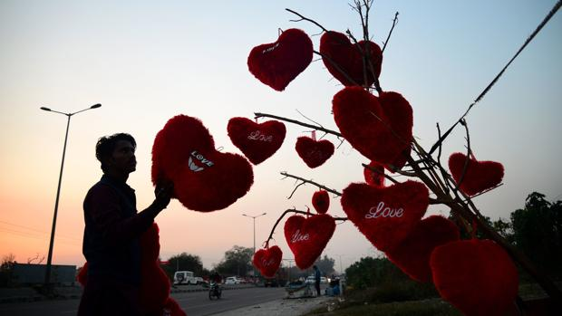 Fotografía de archivo de un vendedor que coloca su mercancía, cojines de regalo para San Valentín, en un árbol