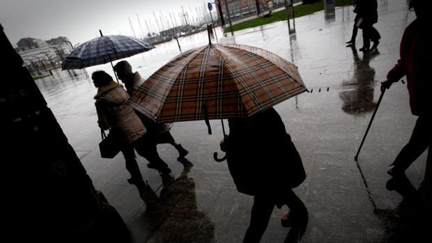 Varias personas caminan bajo la lluvia por una céntrica calle de A Coruña