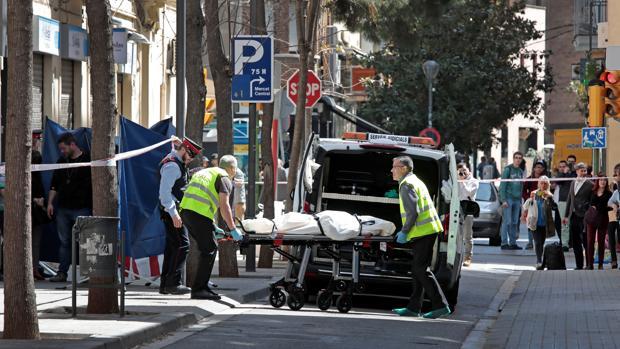 Agentes del servicio funerario transportan el cadáver de la mujer asesinada en Sabadell