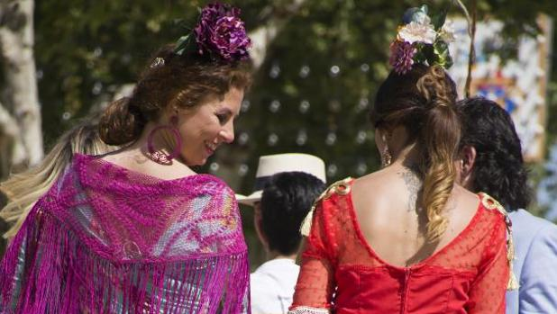 Dos chicas se pasean en coche de caballos por el Real de la Feria de Abril de Sevilla en una jornada en la que el calor es el protagonista