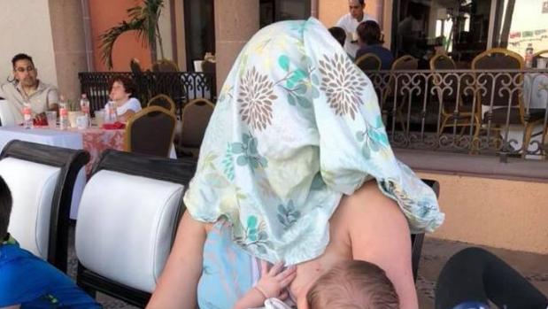 La mujer, con un pañuelo en la cabeza al dar el pecho a su bebé