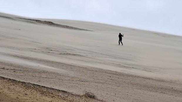 Una persona mide la velocidad del viento en el Pilat Dune cerca de Arcachon, suroeste de Francia, también asediada por la tormenta Gabriel