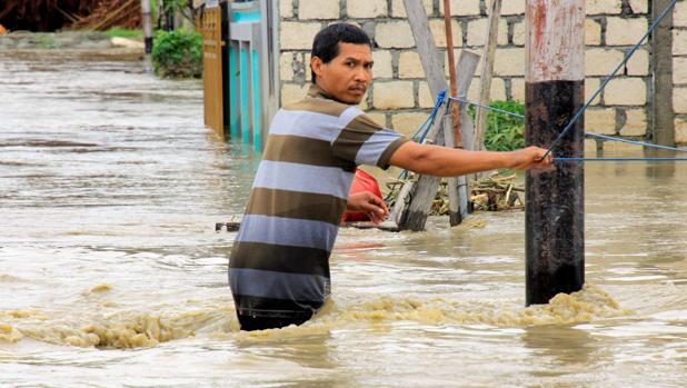 Un residente cruza una calle inundada este lunes en Sentani