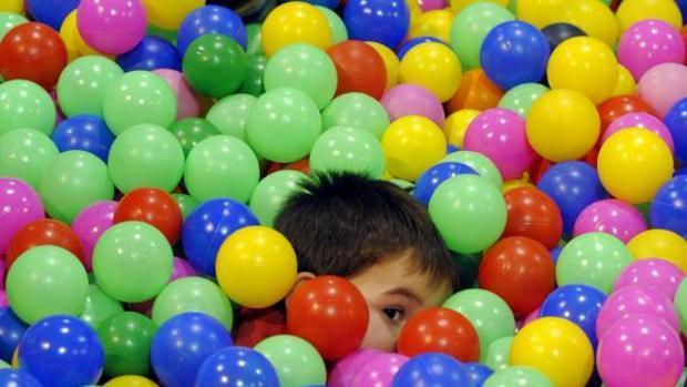 Un niño juega en una piscina de bolas
