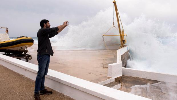 Un hombre fotografía el oleaje en el paseo marítimo de la urbanización S'Algar, en el municipio de Sant Lluís (Menorca)