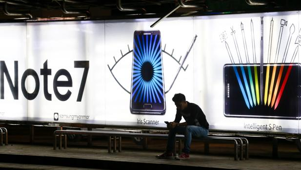 Un hombra espera en una parada de autobús en la que aparece una publicidad del Galaxy Note 7 de Samsung en Rangún