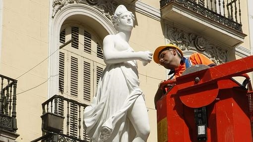 Un operario ultima la colocación de la estatua de la Mariblanca, en la esquina de Sol con la calle Arenal