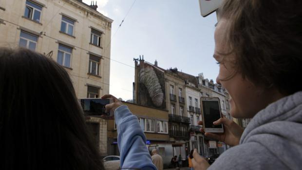 Dos personas fotografían uno de los grafitis de alto contenido sexual que han aparecido en Bruselas