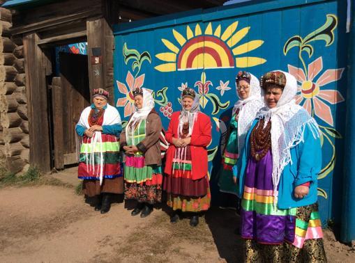 Un grupo de mujeres de Desyatnikovo, vestidas con los trajes tradicionales, esperan a los visitantes para enseñarles sus costumbres y canciones