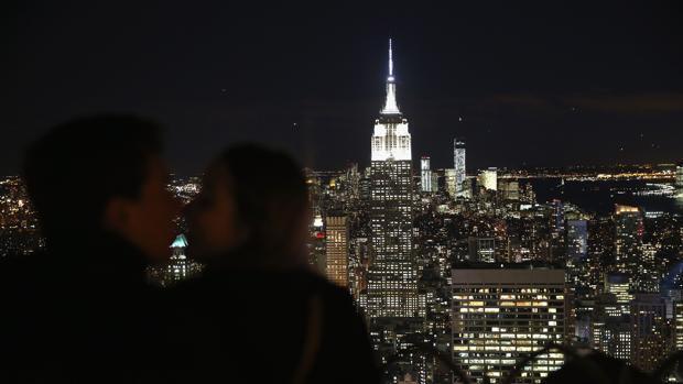 Una pareja se besa con vistas al Empire State Building y al World Trade Center