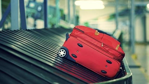 Una maleta en una cinta transportada de aeropuerto
